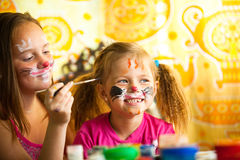 Systrar som leker med målning Royaltyfri Foto