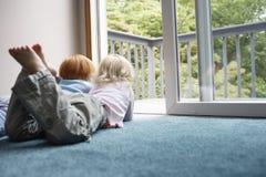 Systrar som ser till och med balkong, medan ligga på matta Arkivfoton