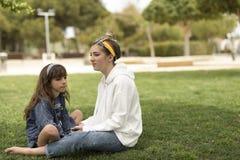 Systrar som sitter på gräset med allvarliga framsidor royaltyfri bild