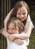Systrar som spelar och kramar Fotografering för Bildbyråer