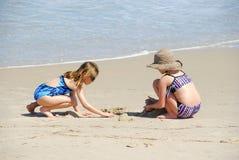 Systrar som spelar på stranden Arkivbild