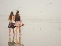 Systrar som tillsammans tycker om tid på den dimmiga stranden Arkivbild