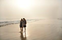 Systrar som tillsammans tycker om tid på den härliga dimmiga stranden Royaltyfri Bild