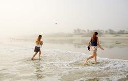 Systrar som tycker om tid på den härliga dimmiga stranden Royaltyfri Bild