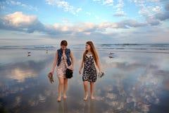 Systrar som tycker om tid på den härliga stranden Royaltyfri Bild