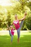 Systrar som utomhus gör övning Sund livsstil arkivfoto