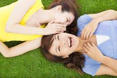 Systrar som viskar på ängen och det lyckliga uttryckt Royaltyfri Foto
