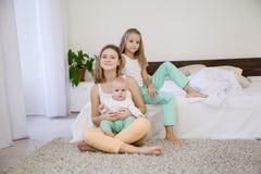 Systrar spelar med behandla som ett barn på sängen i sovrummet Fotografering för Bildbyråer