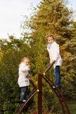 Systrar svärmer upp stege på lekplats royaltyfri fotografi