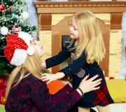 2 systrar vid julgranen Royaltyfri Bild