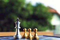 Szachowa deska, srebny królewiątko stojak przy przodem trzy pionek obraz royalty free