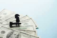 Szachowej gry postacie i USA dolary na błękitnym tle z selekcyjną ostrością, strategii biznesowej planować obraz royalty free