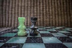 Szachowi kawałki na marmurowym chessboard fotografia stock