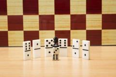 Szachowy koń na kostka do gry i domina na szachowej deski tle Obraz Stock