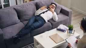 Szalenie faceta pomyślny biznesmen opowiada gestykulować podczas wizyty psycholog zbiory