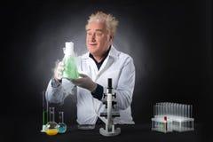 Szalenie klinicysta studiuje w laboratorium i mienia kolbie Zdjęcia Stock