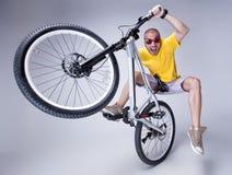 Szalona chłopiec na brudu skoku rowerze na popielatym tle -  Zdjęcie Royalty Free