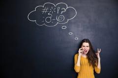 Szalona kobieta krzyczy na telefonie komórkowym stoi nad chalkboard tłem Fotografia Royalty Free