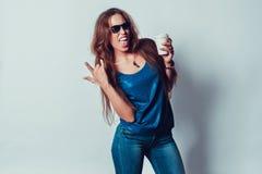 Szalona kobieta w okularach przeciwsłonecznych pokazuje jęzor skałę dalej Fotografia Stock