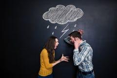 Szalona para wrzeszczy pod patroszonym raincloud nad blackboard tłem obraz stock