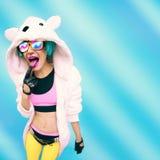 Szalona partyjna dziewczyna w hoodie niedźwiedziu na błękitnym tle pozytywy Obrazy Stock