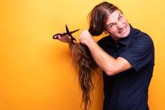 Szalonego gniewnego mężczyzna tnący włosy z nożycami fotografia royalty free