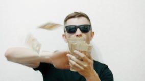 Szalony śmieszny mężczyzna w okularach przeciwsłonecznych rzuca pieniądze, luksusowy życie zdjęcie wideo