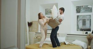 Szalony czas dla pięknej pary w nowożytnej sypialni, bawić się z poduszkami na łóżkowy ono uśmiecha się i dobrego nastrój zdjęcie wideo
