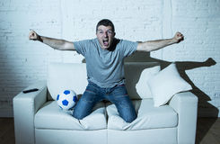 Szalony fan piłki nożnej ogląda tv mecz piłkarskiego samotnie krzyczeć szczęśliwego odświętność cel Fotografia Royalty Free
