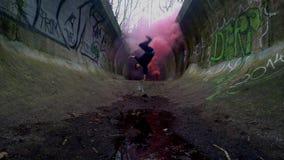 Szalony nastolatek skacze na ręce z czerwień dymem, 4K zdjęcie wideo