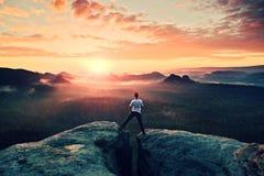 Szalony skokowy wycieczkowicz w czerni świętuje triumf między dwa skalistymi szczytami nad mgła Cudowny jesień brzask Zdjęcia Royalty Free