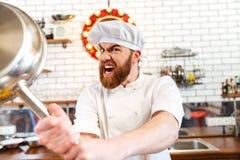 Szalony szalenie szefa kuchni kucharza grożenie z smażyć nieckę obrazy royalty free