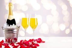 Szampańska butelka z szkłami i czerwonymi różami obraz stock