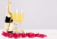 Szampańska butelka z szkłami i różami przeciw neutralnemu tłu fotografia stock