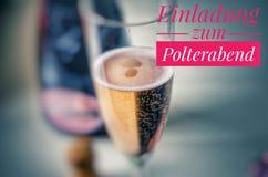Szampański szkło z szlachetnym szampanem i inskrypcją w menchiach w niemiec Einladung zum Polterabend w angielskim zaproszeniu po zdjęcia stock