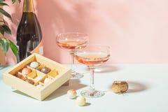 Szampan lub wino w eleganckich szkłach, pudełko czekolady różowy tło jaskrawy światło kosmos kopii Selekcyjna ostro?? obrazy stock