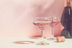 Szampan lub wino w eleganckich szk?ach na r??owego t?a jaskrawym ?wietle kosmos kopii Selekcyjna ostro?? fotografia stock