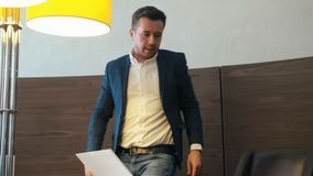Szanowany mężczyzna opowiada smartphone i obsiadaniem przy desktop w biznesowym biurze zbiory