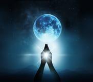 Szanuje i ono modli się na błękitnym księżyc w pełni z natury tłem zdjęcie stock