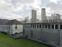 Szara fabryka z zielonymi drzewami i parking fotografia stock