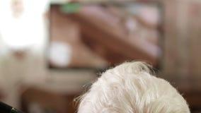 Szara głowa starszy mężczyzna ogląda telewizję Tylni widok, poruszająca kamera zdjęcie wideo