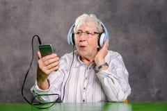Szarej kosmatej starszej kobiety słuchająca muzyka Zdjęcia Royalty Free