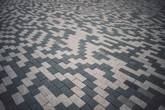 Szarości i białych wzorzyste brukowanie płytki z powodu ulicy, perspektywiczny widok Cementowa cegła obciosujący kamienny podłogo obraz stock