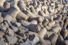 Szarość falochronu betonowi bloki wypiętrzający ochraniać wybrzeże w ciepłym wieczór świetle obraz stock