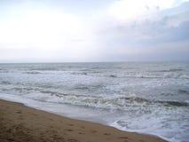 Szarość koloru morze z białą koloru morza pianą na wodnym i brown piasku na plaży Zdjęcia Royalty Free