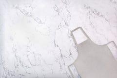 Szary kuchenny fartuch na marmurowej teksturze jako tło zdjęcia royalty free