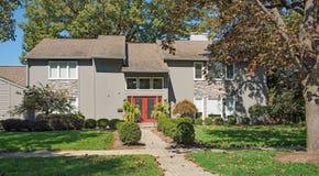 Szary Nowożytny dom z Czerwonymi drzwi & kamienia akcentami Zdjęcia Royalty Free