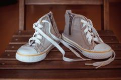 Szarzy dzieci sneakers na drewnianym tle Zdjęcia Stock