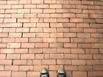 Szarzy sneakers stoi na pomarańczowej ceglanej bruk tekstury podłodze zdjęcie stock