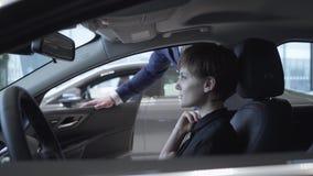 Szczęśliwa śliczna młoda dziewczyna w pasażerskim przedziale nowy samochód Pomyślna kobieta egzamininuje nowego samochód Przedsta zbiory